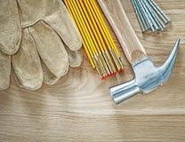 Η σύνθεση της ασφάλειας φορά γάντια στα ξύλινα καρφιά μετάλλων σφυριών μετρητών επάνω Στοκ φωτογραφίες με δικαίωμα ελεύθερης χρήσης