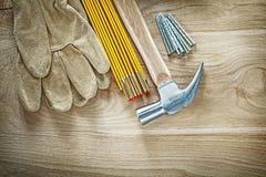 Η σύνθεση της ασφάλειας φορά γάντια στα ξύλινα καρφιά σφυριών νυχιών μετρητών στο W Στοκ φωτογραφία με δικαίωμα ελεύθερης χρήσης