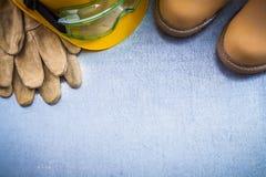 Η σύνθεση του αδιάβροχου δέρματος μποτών ασφάλειας φορά γάντια στην οικοδόμηση χ Στοκ Εικόνα