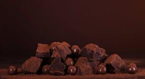Η σύνθεση των κομματιών της σκοτεινής σοκολάτας και ο κύκλος των σοκολατών στο κακάο κονιοποιούν στο καφετί υπόβαθρο στοκ εικόνα με δικαίωμα ελεύθερης χρήσης