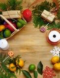 Η σύνθεση Χριστουγέννων που αποτελείται από τα εσπεριδοειδή, γλυκά, thuja διακλαδίζεται και παρόντα κιβώτια Έννοια της συσκευασία Στοκ Φωτογραφία