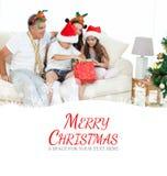 Η σύνθετη εικόνα της οικογένειας στη ημέρα των Χριστουγέννων που εξετάζει το τους παρουσιάζει στο σπίτι Στοκ Εικόνες