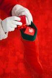 Η σύνθετη εικόνα της τοποθέτησης Άγιου Βασίλη παρουσιάζει στις γυναικείες κάλτσες Χριστουγέννων Στοκ φωτογραφία με δικαίωμα ελεύθερης χρήσης