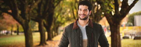 Η σύνθετη εικόνα του χαμογελώντας ατόμου με παραδίδει τις τσέπες που θέτουν στο άσπρο κλίμα Στοκ Εικόνες