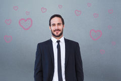 Η σύνθετη εικόνα του χαμογελώντας επιχειρηματία στο κοστούμι που στέκεται με παραδίδει τις τσέπες Στοκ Φωτογραφίες