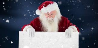 Η σύνθετη εικόνα του santa κρατά ένα σημάδι και κοιτάζει κάτω Στοκ φωτογραφία με δικαίωμα ελεύθερης χρήσης