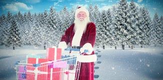 Η σύνθετη εικόνα του santa ωθεί ένα κάρρο αγορών με παρουσιάζει Στοκ Εικόνες