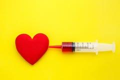 Η σύριγγα δίνει την ιατρική στην κόκκινη μορφή καρδιών στο κίτρινο υπόβαθρο U Στοκ Φωτογραφία