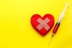 Η σύριγγα δίνει την ιατρική στην κόκκινη μορφή καρδιών στο κίτρινο υπόβαθρο U Στοκ φωτογραφίες με δικαίωμα ελεύθερης χρήσης
