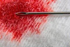 Η σύριγγα βελόνων στην επιφάνεια βαμβακιού με το αίμα είναι μακρο Στοκ Εικόνες