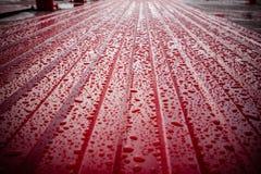 Η σύσταση της κόκκινης επιτροπής σάντουιτς που καλύπτεται με τις σταγόνες βροχής στοκ φωτογραφίες με δικαίωμα ελεύθερης χρήσης