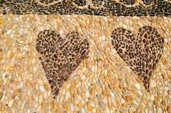 Η σύσταση του τοίχου πετρών, ο δρόμος από τις μικρές στρογγυλές και ωοειδείς πέτρες με τις αφαιρεμένες γραμμές σχεδίων δύο καρδιώ στοκ φωτογραφίες