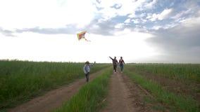 Η τέλεια οικογένεια, παιδί με τον ικτίνο στα χέρια τρέχει κοντά στους νέους γονείς στην επαρχία στο υπόβαθρο του ηλιόλουστου ουρα απόθεμα βίντεο
