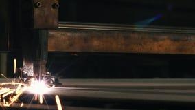 Η τέμνουσα μηχανή λέιζερ κινηματογραφήσεων σε πρώτο πλάνο κόβει ένα φύλλο του μετάλλου φιλμ μικρού μήκους