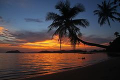 Η ταλάντευση ή το λίκνο κρεμά στο όμορφο ηλιοβασίλεμα σκιών δέντρων καρύδων koh Mak στην παραλία παραδοσιακή Ταϊλάνδη νησιών Στοκ φωτογραφία με δικαίωμα ελεύθερης χρήσης