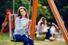 Η ταλάντευση εφήβων σπουδαστών κοριτσιών σε μια ταλάντευση και η χρησιμοποίηση του τηλεφώνου για την επικοινωνία κοιτάζουν στο πλ στοκ φωτογραφία με δικαίωμα ελεύθερης χρήσης