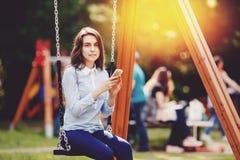 Η ταλάντευση εφήβων σπουδαστών κοριτσιών σε μια ταλάντευση και η χρησιμοποίηση του τηλεφώνου για την επικοινωνία κοιτάζουν στο πλ στοκ εικόνες με δικαίωμα ελεύθερης χρήσης