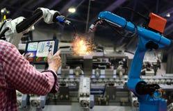Η ταμπλέτα μηχανικών ελέγχει την παραγωγή των ρομπότ βιομηχανίας κατασκευής μερών εργοστασίων Στοκ Εικόνες