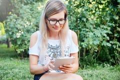 Η ταμπλέτα Όμορφο κορίτσι που εργάζεται σε μια ταμπλέτα σύγχρονες τεχνολογίες Γυναίκα με μια ταμπλέτα στη φύση Στοκ εικόνα με δικαίωμα ελεύθερης χρήσης