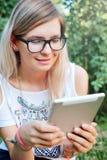 Η ταμπλέτα Όμορφο κορίτσι που εργάζεται σε μια ταμπλέτα σύγχρονες τεχνολογίες Γυναίκα με μια ταμπλέτα στη φύση Στοκ Φωτογραφία