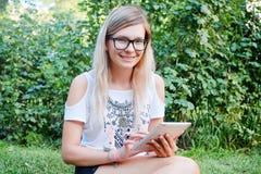 Η ταμπλέτα Όμορφο κορίτσι που εργάζεται σε μια ταμπλέτα σύγχρονες τεχνολογίες Γυναίκα με μια ταμπλέτα στη φύση Στοκ φωτογραφία με δικαίωμα ελεύθερης χρήσης
