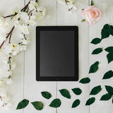 Η ταμπλέτα, ρόδινη αυξήθηκε λουλούδι, πράσινοι φύλλα και κλάδος sakura στο άσπρο ξύλινο γραφείο Η τοπ άποψη, επίπεδη βάζει Στοκ Φωτογραφία
