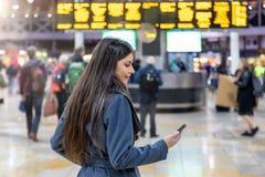 Η ταξιδιωτική γυναίκα ελέγχει το κινητό τηλέφωνό της σε έναν πολυάσχολο σταθμό τρένου στοκ φωτογραφία