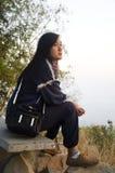 Η ταξιδιωτική ταϊλανδική γυναίκα κάθεται και θέτοντας για πάρτε τη φωτογραφία στην άποψη πάνω από το βουνό phu tok Στοκ Εικόνα