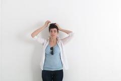 Η ταραγμένη διασκεδάζοντας αστεία νέα γυναίκα με ακατάστατο τα κοντά σκοτεινά χέρια εκμετάλλευσης τρίχας στο κεφάλι της σε ανοικτ Στοκ Εικόνες