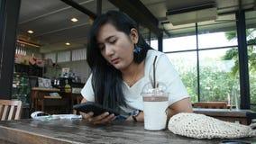 Η ταϊλανδική γυναίκα κάθεται χαλαρώνει το smartphone παιχνιδιού και τη σοκολάτα ποτών frappe στη καφετερία απόθεμα βίντεο