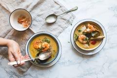 Η ταϊλανδική σούπα του Tom Yum Goong με τις γαρίδες, τις γαρίδες και kaffir τα φύλλα εξυπηρέτησε σε μια άσπρη μαρμάρινη σύσταση στοκ φωτογραφία με δικαίωμα ελεύθερης χρήσης