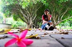 Η ταϊλανδική τοποθέτηση γυναικών και κάθεται στο πάτωμα με Plumeria ή Templetree Φ Στοκ φωτογραφία με δικαίωμα ελεύθερης χρήσης