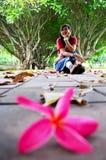 Η ταϊλανδική τοποθέτηση γυναικών και κάθεται στο πάτωμα με Plumeria ή Templetree Φ Στοκ φωτογραφίες με δικαίωμα ελεύθερης χρήσης