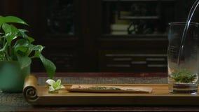 Η τελετή τσαγιού Η γυναίκα χύνει το ζεστό νερό teapot με το τσάι Teapot γυαλιού με το ανθίζοντας λουλούδι τσαγιού μέσα απόθεμα βίντεο