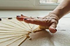 Η τεμαχισμένη ακατέργαστη μικτή ζύμη με τα μούρα βρίσκεται στο δίσκο ψησίματος μαγειρεύοντας πιάτο ψησίματος τα χέρια των γυναικώ στοκ εικόνα με δικαίωμα ελεύθερης χρήσης
