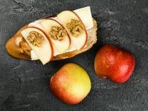 Η τεμαχισμένη Apple με το τυρί της Brie και ξύλα καρυδιάς σε ψημένο Baguette Στοκ Φωτογραφία