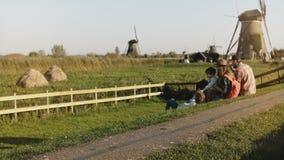 Η τετραμελής οικογένεια κάθεται μαζί κοντά σε ένα αγρόκτημα ανεμόμυλων Το Mom, μπαμπάς και δύο παιδιά απολαμβάνουν το ηλιόλουστο  φιλμ μικρού μήκους