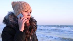 Η τηλεφωνική επικοινωνία, θηλυκό μιλά στο smartphone στην εν πλω ακτή Σαββατοκύριακου φιλμ μικρού μήκους
