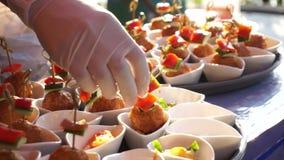 Η τηλεοπτική επιχείρηση τομέα εστιάσεως, χέρι αρχιμαγείρων με το γάντι προετοιμάζει τα τρόφιμα κομμάτων κοκτέιλ απόθεμα βίντεο