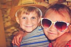Η τονισμένη εικόνα ενός κοριτσιού στα γυαλιά ηλίου, αγκαλιάζει το μικρότερο αδερφό της Στοκ Φωτογραφίες