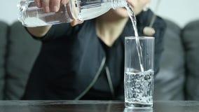 Η τονισμένη καταθλιπτική αυτοκαταστροφική νέα γυναίκα γεμίζει το νερό στο ποτήρι, σε αργή κίνηση κίνηση αργή φιλμ μικρού μήκους