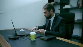 Η τονισμένη συνεδρίαση επιχειρηματιών στο γραφείο πίσω από το lap-top, άνδρας εργαζόμενος εξετάζει το τηλέφωνο και παίρνειη, αργό απόθεμα βίντεο