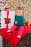 Η τοποθέτηση αγοριών οικογενειακών παιδιών Χριστουγέννων στο ξύλινο κιβώτιο κοντά παρουσιάζει και άσπρο φανταχτερό νέο δέντρο έτο στοκ εικόνα με δικαίωμα ελεύθερης χρήσης