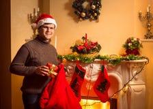 Η τοποθέτηση ατόμων χαμόγελου παρουσιάζει στις γυναικείες κάλτσες Χριστουγέννων που κρεμούν στο φ Στοκ Εικόνες