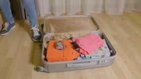 Η τοποθέτηση γυναικών γεμίζει και ενδύματα στη βαλίτσα ταξιδιού στο πάτωμα στο εγχώριο δωμάτιο φιλμ μικρού μήκους