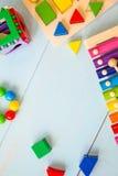 Η τοπ άποψη ή επίπεδος βάζει στα ζωηρόχρωμα παιχνίδια στο ξύλινο υπόβαθρο με το διάστημα αντιγράφων Θερμό εκλεκτής ποιότητας φίλτ Στοκ Εικόνες