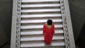 Η τοπ άποψη, γυναίκα στο μακρύ κομψό κόκκινο φόρεμα στα τακούνια κατεβαίνει μια μεγάλη σκάλα φιλμ μικρού μήκους