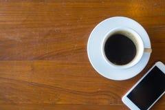 Η τοπ άποψη ενός φλυτζανιού του καυτού καφέ και το smartphone βάζουν παλαιό σε ξύλινο Στοκ Φωτογραφίες