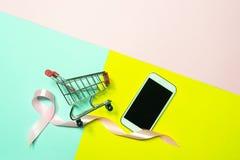 Η τοπ άποψη, επίπεδη βάζει το κάρρο αγορών smartphone με τη ρόδινη κορδέλλα στο δ στοκ εικόνες με δικαίωμα ελεύθερης χρήσης
