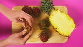 Η τοπ άποψη, θηλυκά χέρια καθαρίζει rambutan σε έναν ξύλινο πίνακα Η έννοια των φυσικών υγιών τροφίμων απόθεμα βίντεο